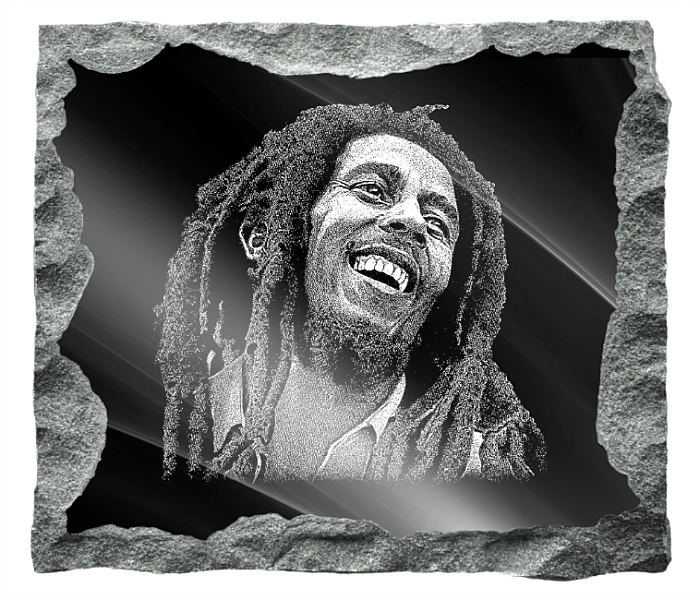 Memorial image of Bob Marley etched on a black granite background