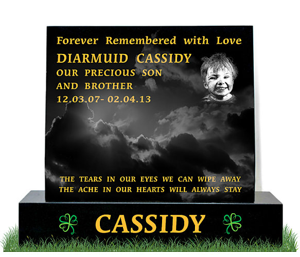 Small Head-block Headstone in Black Granite. Etched portrait on top right and two modern shamrocks etched either side of the surname. Inscriptions engraved in gold leaf. Font: Times Roman 76 lettering.