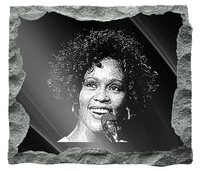Memorial image of Whitney Houston etched on a black granite background