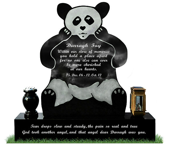 Teddy Bear Gravestone in Black Granite. A round granite flower vase and a bronze solar light rest each side of the base. All inscriptions engraved in silver. Font: Script Bold lettering.