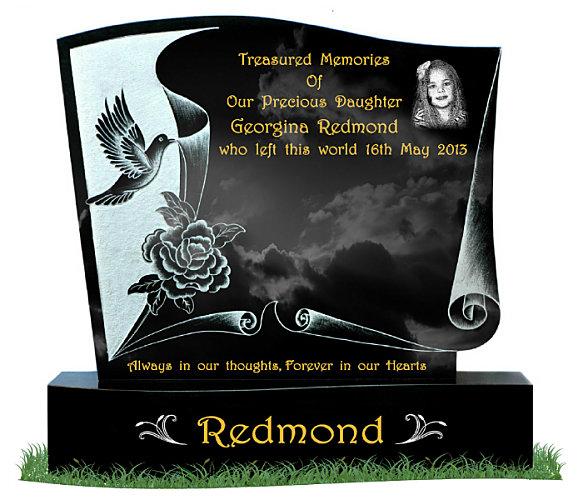 Page Scroll Headstone in Black Granite. Etched image of dove, flowers and page scroll with a silver background. Etched portrait on top right. Two decorative leaves etched in silver each side of the surname on a curved base. Inscriptions engraved in gold leaf. Font: Harrington Script lettering.